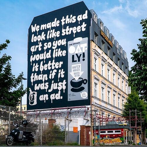 "Black and white Oatly billboard in Berlin. The text is dripping as if just painted on, reading: ""We made this ad look like street art so you would like it better than if it was just an ad."" There is a paint can with paint brush sticking out of the top in the bottom left corner and there is a picture of their oat milk carton to the right of the text."